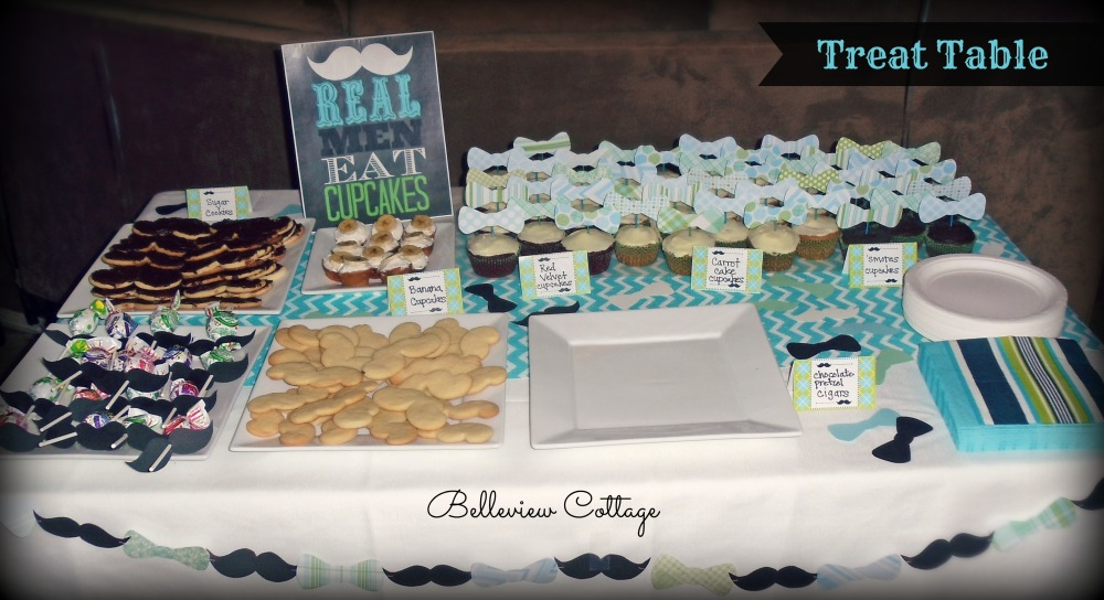 "Treat Table: bowtie cupcake toppers; mustache sugar cookies; chocolate pretzel ""cigars""; mustache suckers; Real Men Eat Cupcakes Sign; and mustache/bowtie garland 